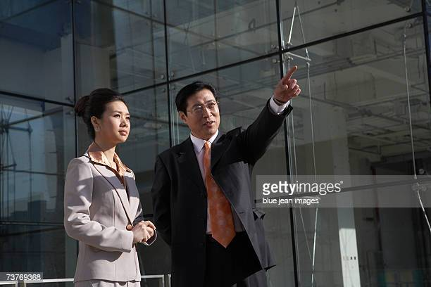 Businessman points to the cityscape as businesswoman looks on