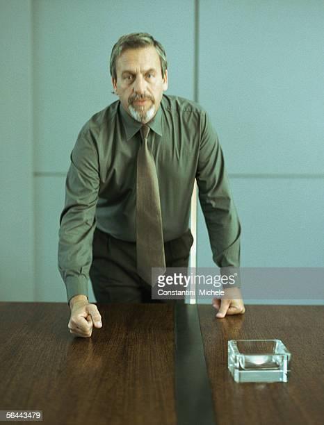 Businessman pounding fist on table, portrait