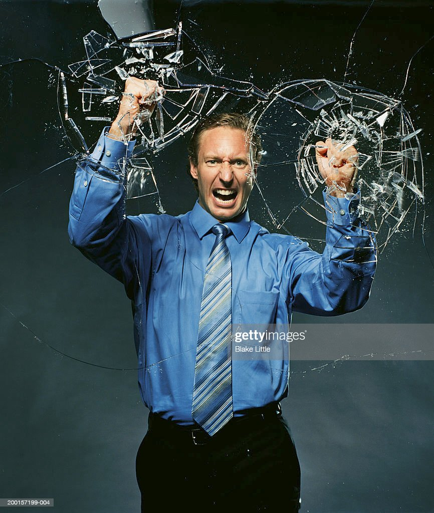 Businessman pounding  glass with fists, glass breaking