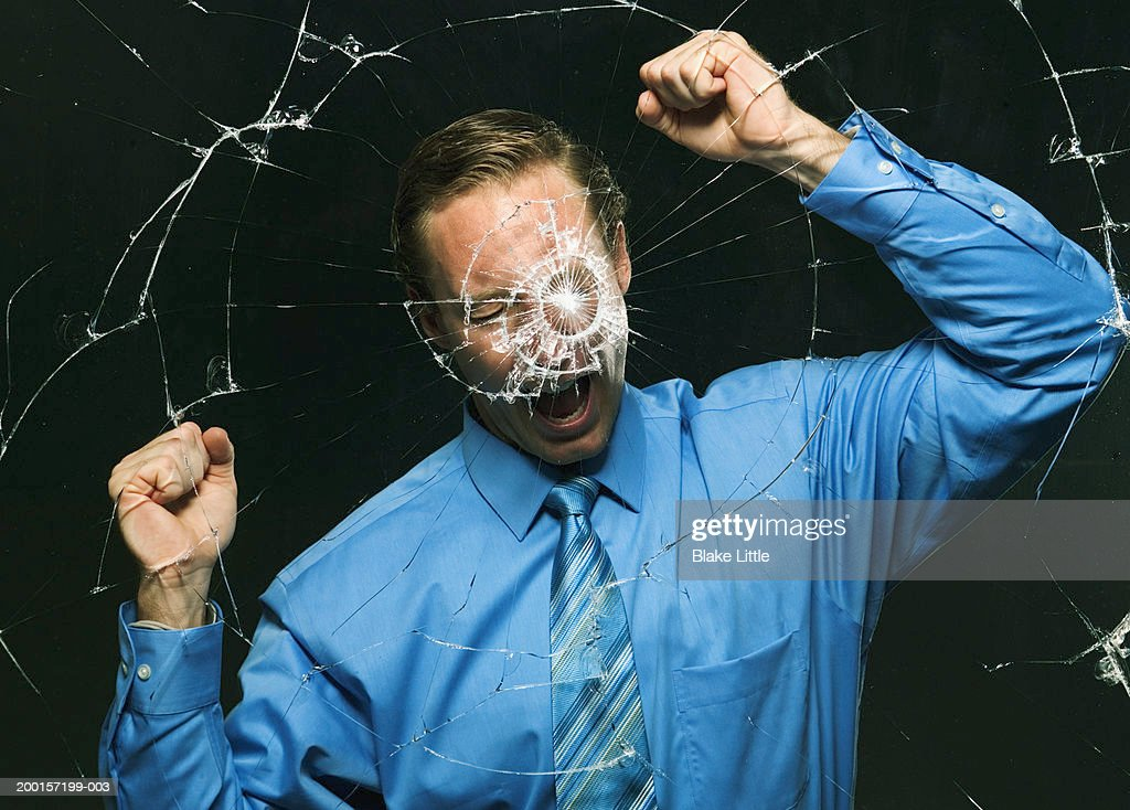 Businessman pounding  glass with fists