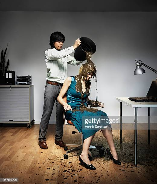 Businessman pouring mud on female colleague