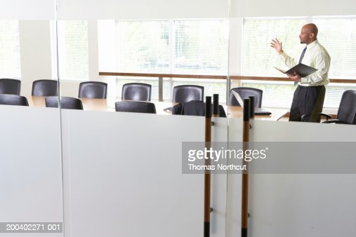 Businessman practicing presentation in boardroom, side view