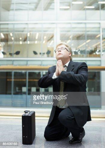 Businessman praying in building lobby