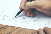 Cropped image of businessman preparing checklist at office desk