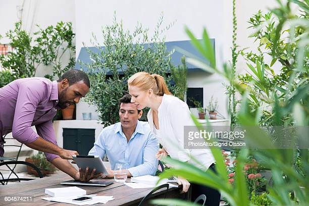 Businessman presenting ideas displayed on digital tablet to colleagues