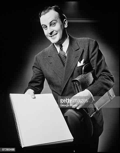 Businessman presenting notebook, (B&W), portrait