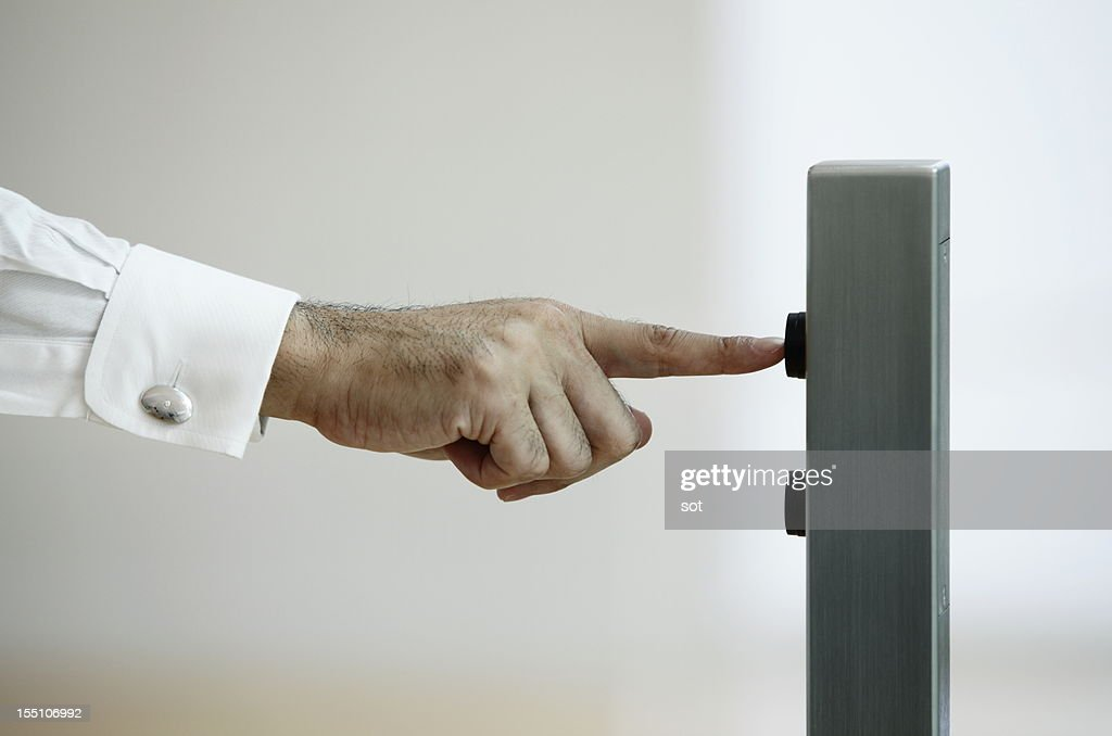 Businessman pressing button for elevator,close up