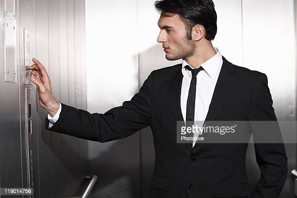 Businessman pressing elevator buttons