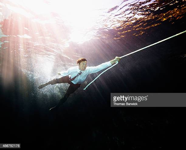 Businessman pulled by rope underwater