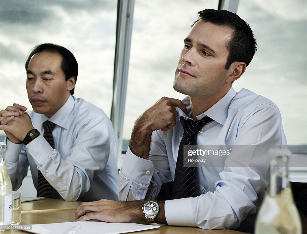 Businessman pulling at collar at conference table meeting : Stock Photo