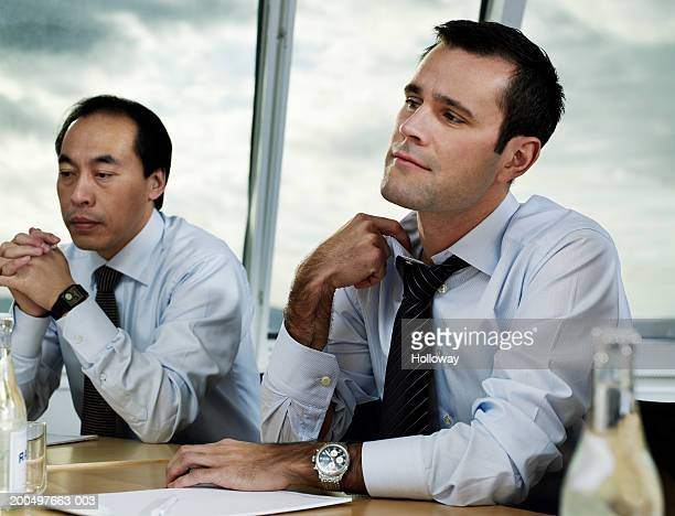 Businessman pulling at collar at conference table meeting