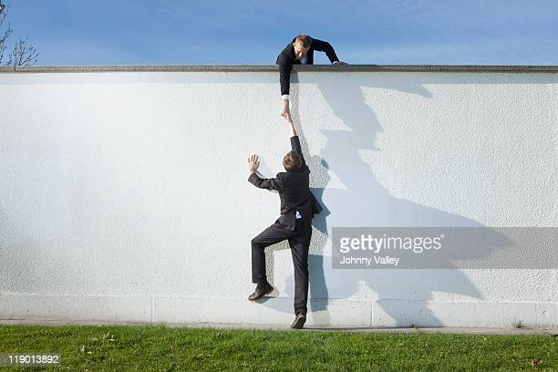 Businessman pulling colleague over wall
