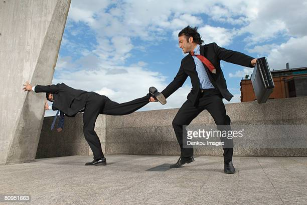 Businessman pulling colleagues leg on windy roof