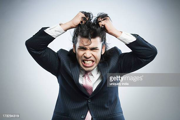 Businessman pulling his hair in frustration