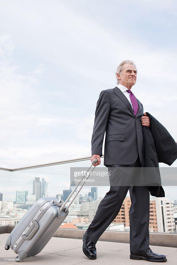 Businessman pulling luggage across urban balcony : Stock Photo