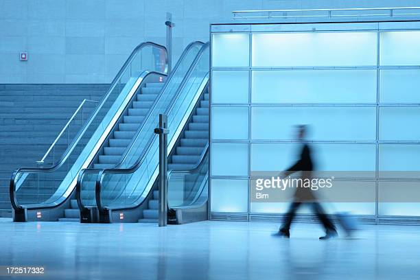 Businessman pulling luggage in corridor with escalators blurred motion