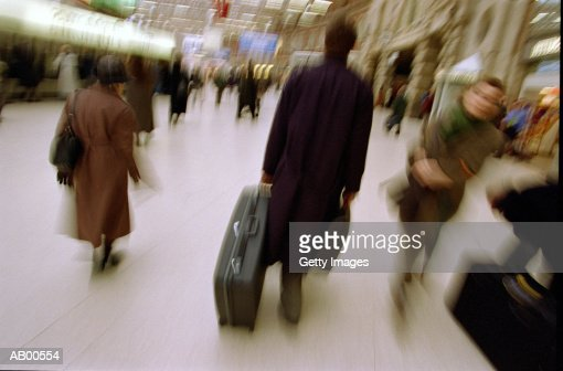 Businessman pulling luggage in train station, rear view : Stock Photo