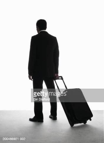 Businessman pulling luggage, rear view : Stock Photo