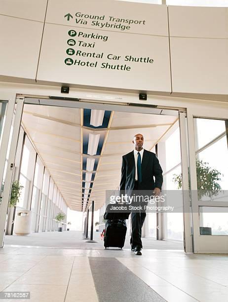 Businessman pulling luggage through airport terminal