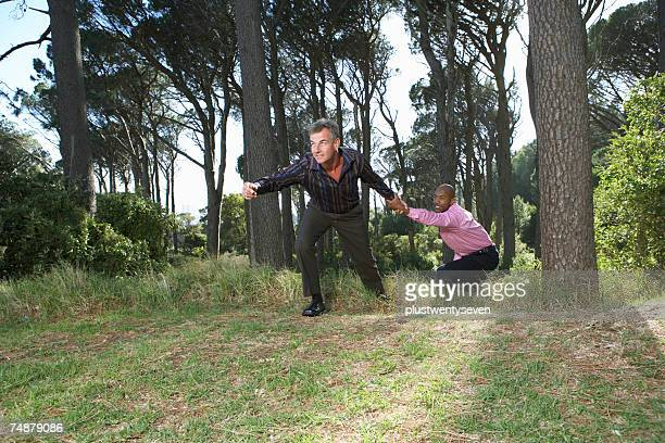 Businessman pulling male colleague from woods