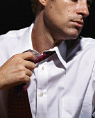 Businessman pulling off tie