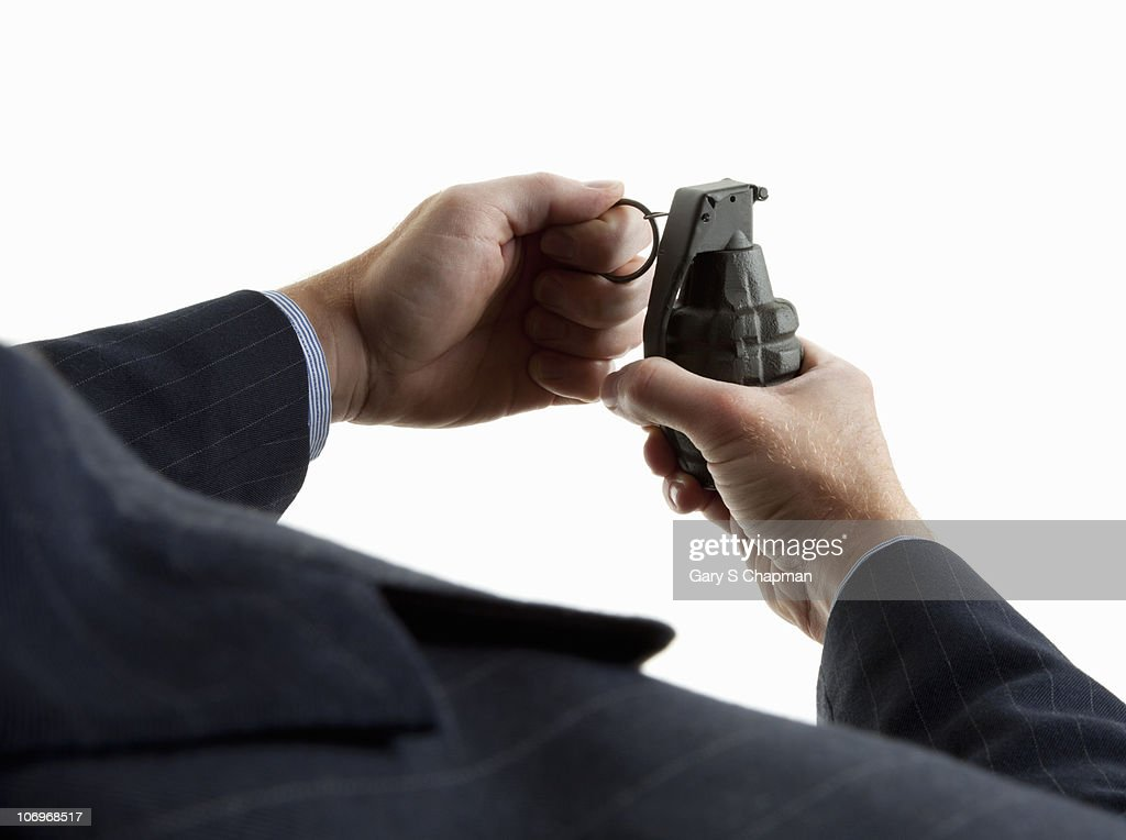 Businessman pulling pin on hand grenade : Stock Photo