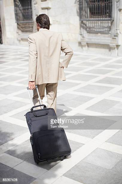 Businessman pulling rolling suitcase