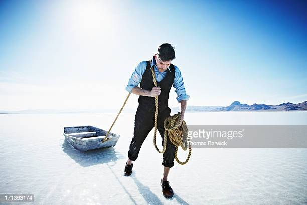 Businessman pulling small boat in shallow water