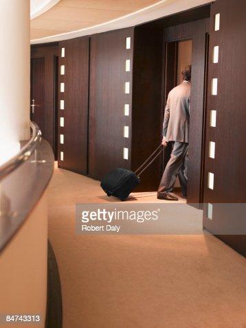 Businessman pulling suitcase into elevator : Stock Photo