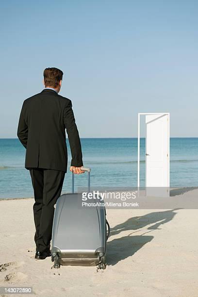 Businessman pulling suitcase on beach, half-open door in background