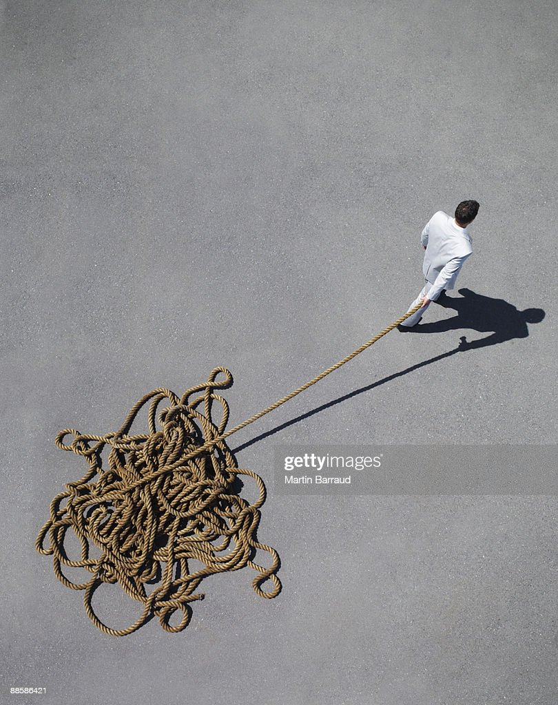 Businessman pulling tangled rope : Stock Photo