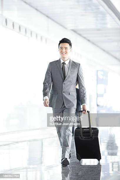 Businessman pulling wheeled luggage in airport lobby