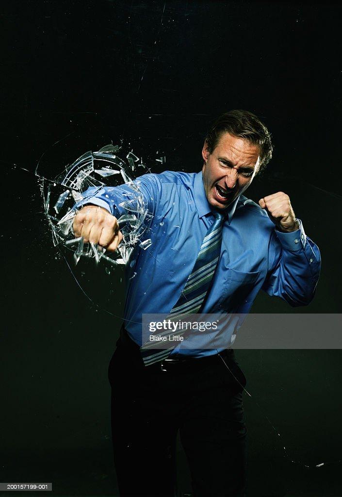 Businessman punching fist through glass