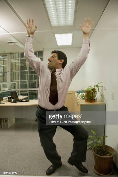 Businessman pushed up against glass wall