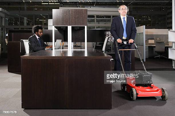Un homme d'affaires en poussant une tondeuse à gazon dans un bureau