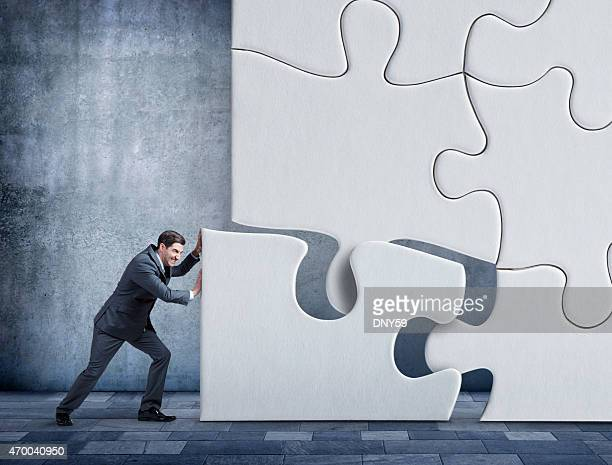 Businessman pushing a puzzle piece into place