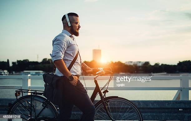Businessman Pushing Bicycle and Listening Music.