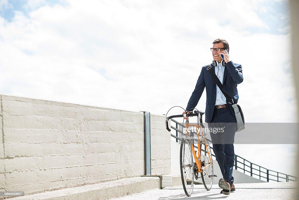 Businessman pushing bike while talking on the phone