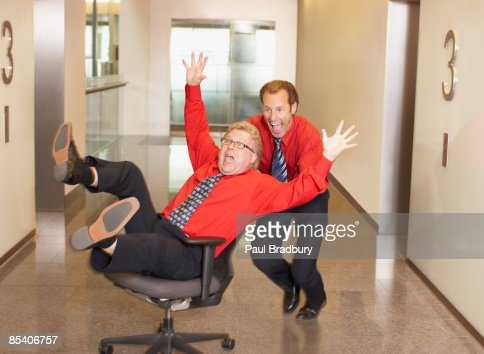 Businessman pushing co-worker in chair in corridor : Stock Photo