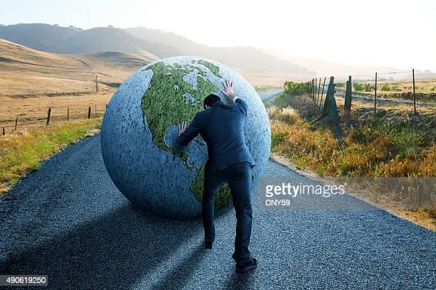 Businessman Pushing Globe Down Rural Road