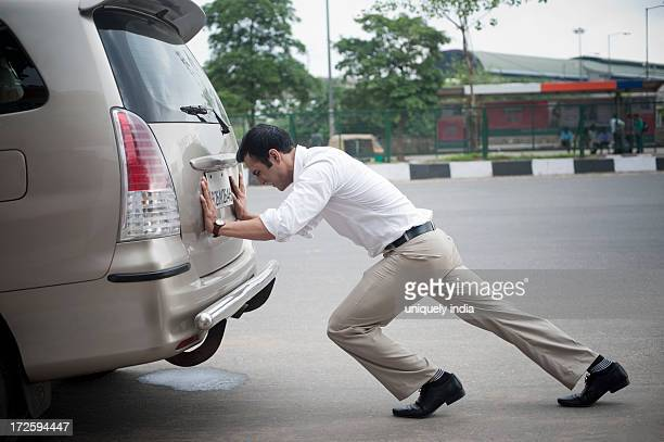Businessman pushing his car
