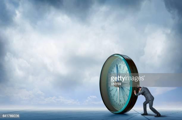 Businessman Pushing Large Compass Across Generic Map