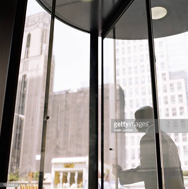 Businessman pushing through revolving doors