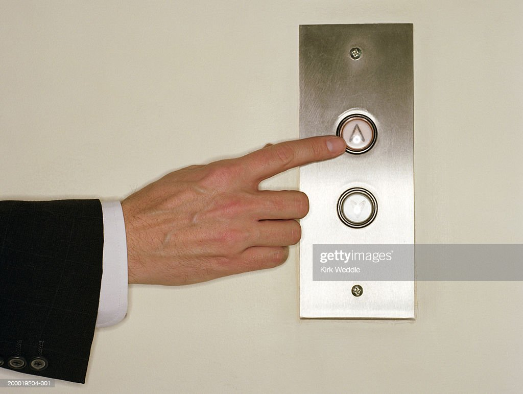 Businessman pushing 'UP' button for elevator, close-up of hand : Stock Photo