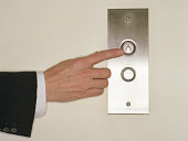 Businessman pushing 'UP' button for elevator, close-up of hand
