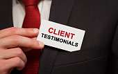 Businessman putting a card with text Client Testimonials in the pocket