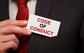 Businessman putting a card with text Code of Conduct in the pocket