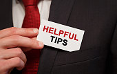 Businessman putting a card with text Helpful tips in the pocket