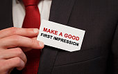 Businessman putting a card with text Make a good first impression in the pocket