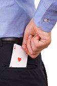 Businessman putting ace card in back pocket.